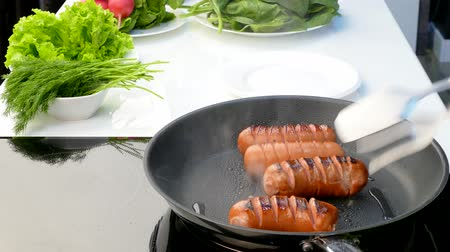 párek v rohlíku : the cook fry up the crust of sausage in a frying pan