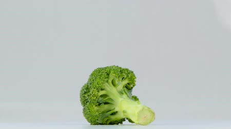 one head of broccoli spinning on white background