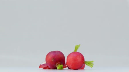 peeled and chopped radish spinning on white background