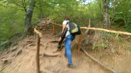 tourer : The camera watches as a man climbs the mountain path.
