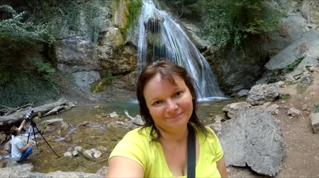 tourer : A girl makes selfie on a waterfall background. Stock Footage