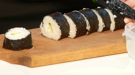 soy : The cook slicks a sushi roll