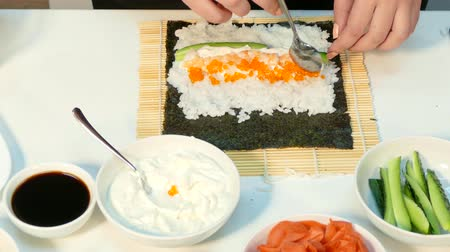 dilis : cooks lay the shrimp and red salmon caviar in the sushi roll stuffing Stock mozgókép