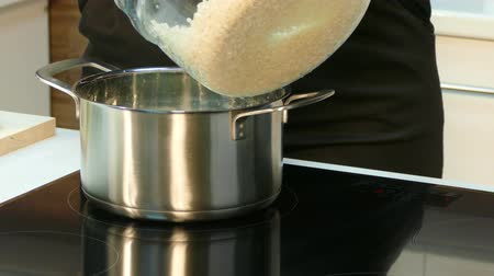induction cooker : Cook put the pot on the stove and fill it with rice