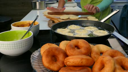 disposição : The cook rolls out the dough and fry donuts. Stock Footage