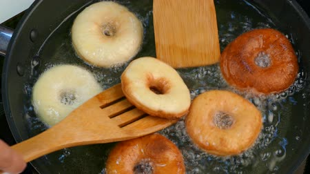 apetitoso : The cook turns the donuts in oil.