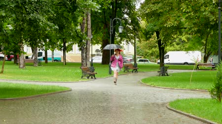 etli : girl with an umbrella jumping on an empty park
