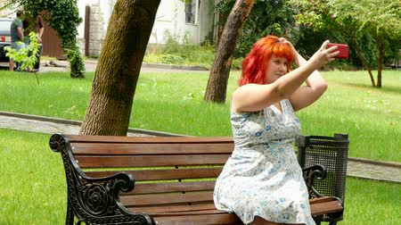etli : Red-haired girl doing selfie on a park bench