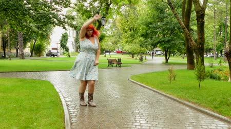 amadurecida : Red-haired girl strangely dancing in the park Stock Footage