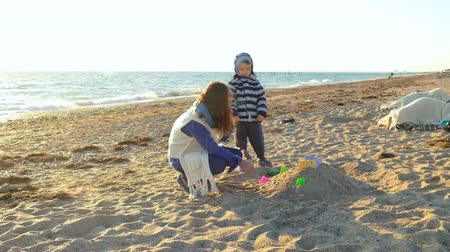 младенчество : Children make a castle of sand.