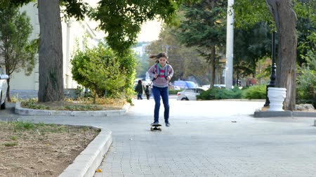 mladistvý : The girl is riding on a skateboard in the park.
