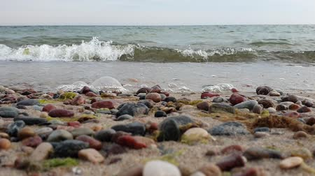 успокаивающий : Waves lapping on the shore. Sandy beach with pebbles. Low point shooting. Colorful pebbles in the foreground in the blur. Waves move directly to the camera Стоковые видеозаписи