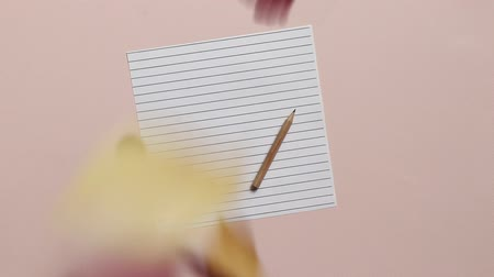 Empty sheet of paper with pencil on pink background. Colorful autumn leaves falling on the page. Concept of back to school