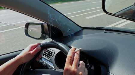 Smoking cigarette in the hand of woman at steering wheel