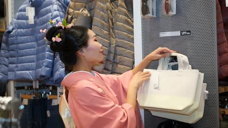 uniqlo : Moscow, Russia - March 5, 2017: Geisha shopping in the UNIQLO clothing store among the clothing goods and ordinary consumers. Performance is timed to the opening of a new 15th store in Russia. Stock Footage