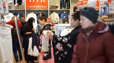 uniqlo : Moscow, Russia - March 5, 2017: Geishas walking in the UNIQLO clothing store among the clothing goods and ordinary consumers. Performance is timed to the opening of a new 15th store in Russia. Stock Footage