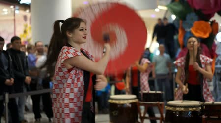 drumbeat : Moscow, Russia - March 4, 2017: group of Japanese Taiko drummers girls perform in Oceania shopping center on the at the opening of a new store UNIQLO Unique Clothing Warehouse. Dance with umbrella.
