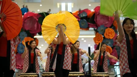 uniqlo : Moscow, Russia - March 5, 2017: group of Japanese Taiko drummers girls perform in Oceania shopping center on the at the opening of a new store UNIQLO Unique Clothing Warehouse. Danse with funs. Stock Footage