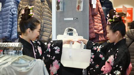 quimono : Moscow, Russia - March 5, 2017: Two geisha shopping in the UNIQLO clothing store among the clothing goods and ordinary consumers. Performance is timed to the opening of a new 15th store in Russia.