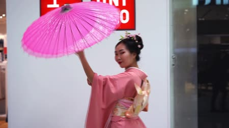 uniqlo : Moscow, Russia - March 5, 2017: Geisha in traditional Japanese kimono with umbrella at the entrance to the uniqlo store. Performance is timed to the opening of a new 15th store in Russia.