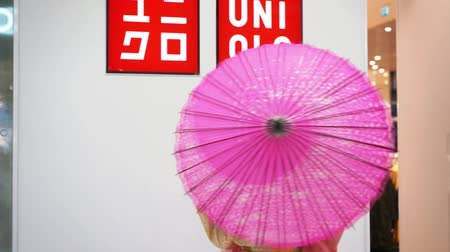 uniqlo : Moscow, Russia - March 5, 2017: Geisha in traditional Japanese kimono with umbrella near the trademark sign of uniqlo store. Performance is timed to the opening of a new 15th store in Russia. Stock Footage