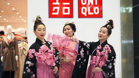 uniqlo : Moscow, Russia - March 5, 2017: Three geisha in traditional Japanese kimono with sakura branches at the entrance to the uniqlo store. Performance is timed to the opening of a new 15th store in Russia.