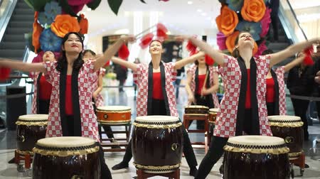 uniqlo : Moscow, Russia - March 5, 2017: group of Japanese Taiko drummers girls perform in Oceania shopping center on the at the opening of a new store UNIQLO Unique Clothing Warehouse. Red drumsticks. Stock Footage