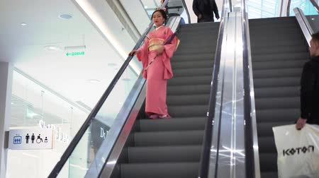 quimono : Moscow, Russia - March 5, 2017: geisha in traditional Japanese kimono rides on an escalator in a mall during the performances in Oceania shopping center