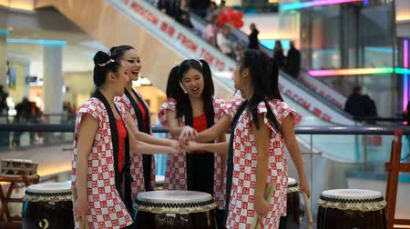 uniqlo : Moscow, Russia - March 25, 2017: Japanese Taiko drummers girls in Kaleidoscope shopping center at the opening of a new store UNIQLO. Girls scream Taiko inspiration and pick up drumsticks.