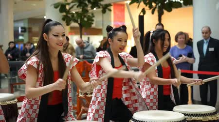 uniqlo : Moscow, Russia - March 25, 2017: group of Japanese Taiko drummers girls perform in Kaleidoscope shopping center at the opening of a new store UNIQLO Unique Clothing Warehouse.