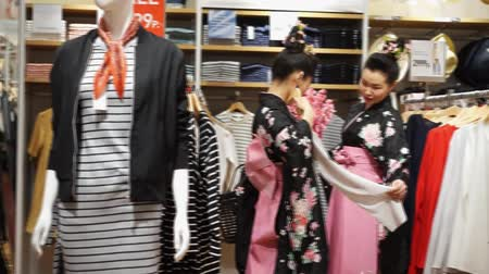 uniqlo : Moscow, Russia - March 24, 2017: group of geisha shopping in the UNIQLO clothing store. Performance is timed to the opening of a new Uniqlo store in Riviera shopping moll.