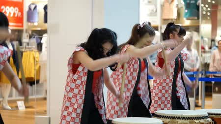 uniqlo : Moscow, Russia - March 24, 2017: group of Japanese Taiko drummers girls perform in Riviera shopping center at the opening of a new store UNIQLO Unique Clothing Warehouse.
