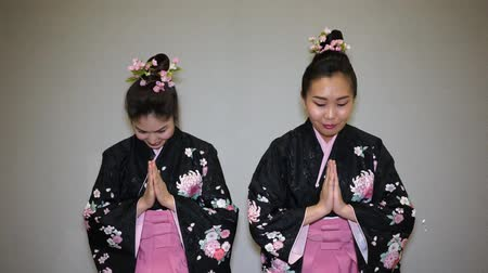 üdvözlettel : Two geisha in traditional japanese kimono greeting