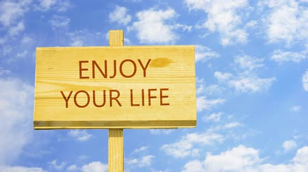 seu : Enjoy your life. Words on a wooden sign.