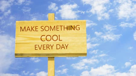 conversa : Make something cool every day. Words on a wooden sign.
