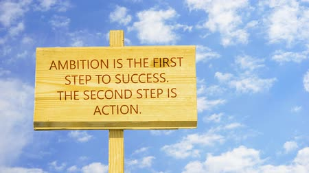 primeiro plano : Ambition is the first step to success, The second step is action. Words on a wooden sign.