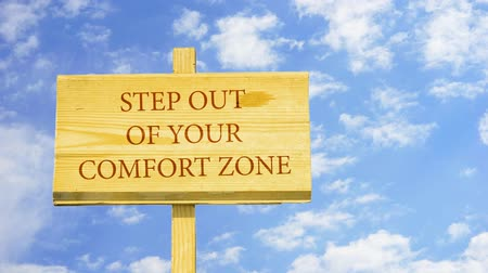 konfor : Step out of your comfort zone. Words on a wooden sign.