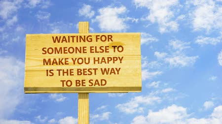 be sad : Waiting for someone else to make you happy is the best way to be sad. Words on a wooden sign.