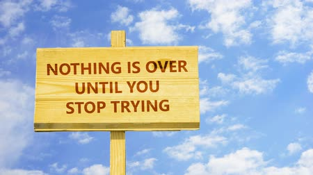 until : Nothing is over until you stop trying. Words on a wooden sign. Stock Footage
