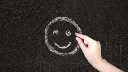 gaining : Hand drawing unhappy and happy smileys on blackboard. Female hand leafing through and choosing the smile.
