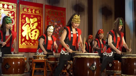 chatter : Moscow, Russia - February 03, 2018: drummer girls from Taiko In-Spirational asian drum show in demons masks perform during the Asian new year concert. Stock Footage