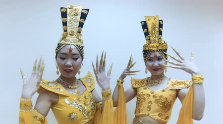 tırnak : Two beautiful asian women dancing with hands with long nail manicure in a traditional thai yellow dress