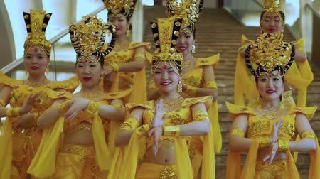 Group of beautiful asian women standing and dancing with hands in a traditional thai yellow dresses and hats