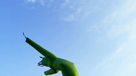 plac zabaw : Inflatable dancing, flailing arms tube guy, against blue sky and clouds