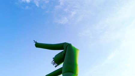 долл : Inflatable dancing, waving hands tube guy, against blue sky and clouds