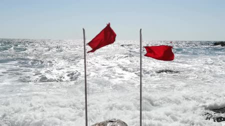 Two beach warning red flags splashing on wind. Stormy sea threat warning. Vacation danger. Extreme seawater caution.