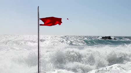 tenger : Beach warning red flag splashing on wind. Stormy sea threat warning. Vacation danger. Extreme seawater caution.