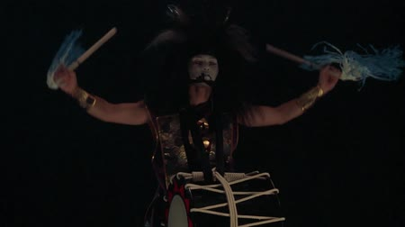 Artist drummer Taiko in a wig with horns and make-up drum on stage against a dark background. Demon from Japanese mythology.