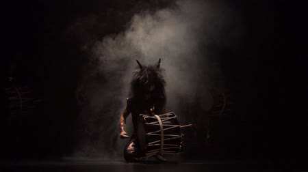 Four artists drummers Taiko in a wig with horns and make-up drum on stage against a dark background with smoke. Demons from Japanese mythology.