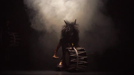рог : Four artists drummers Taiko in a wig with horns and make-up drum on stage against a dark background with smoke. Demons from Japanese mythology.